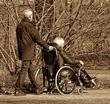 Elderly man pushing his wife in a wheelchair