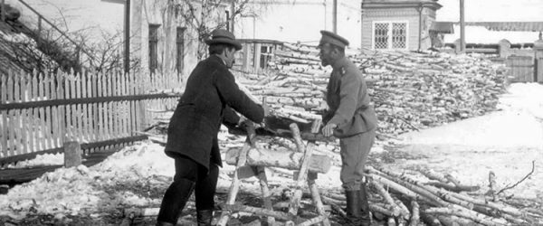 Nicholas II and an unidentified man sawing wood during the captivity at Tobolsk.