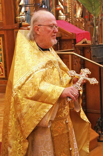 Photo of Fr. David Starr holding the cross at the end of Liturgy