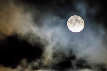 Full moon at night with thin clouds around it