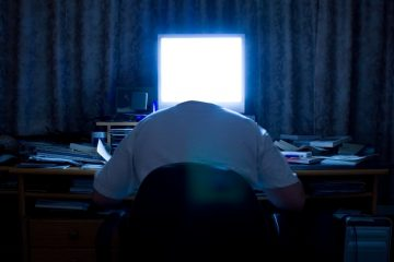 A headless man at a cluttered desk with glowing computer screen