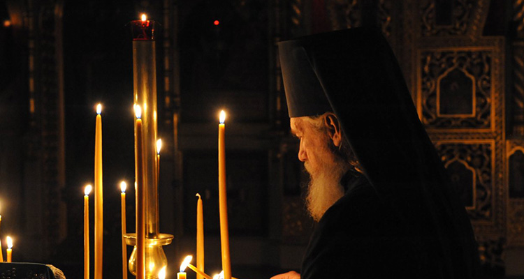 Russian monk lighting candles in church.